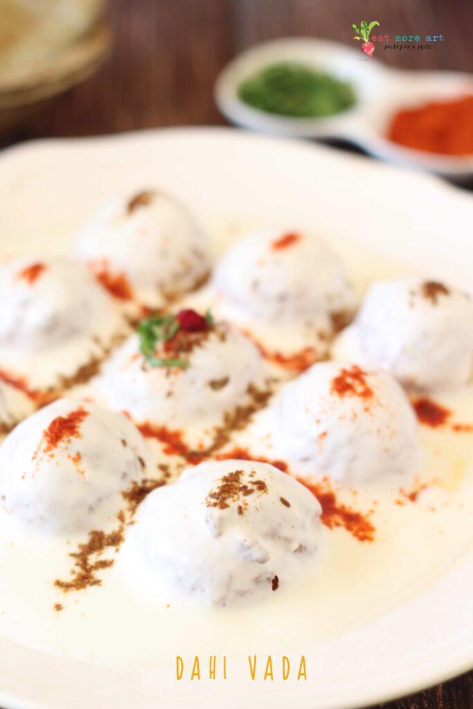 An side closeup shot of dahi vada garnished with cumin and chili powder