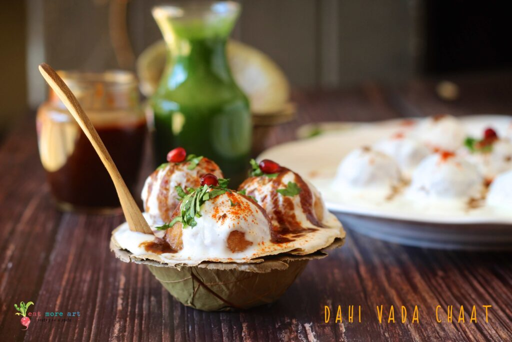 A closeup side shot of Dahi Vada with garnishes in a leaf bowl