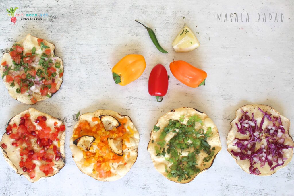 an overhead shot of masala papads topped with colorful vegetables