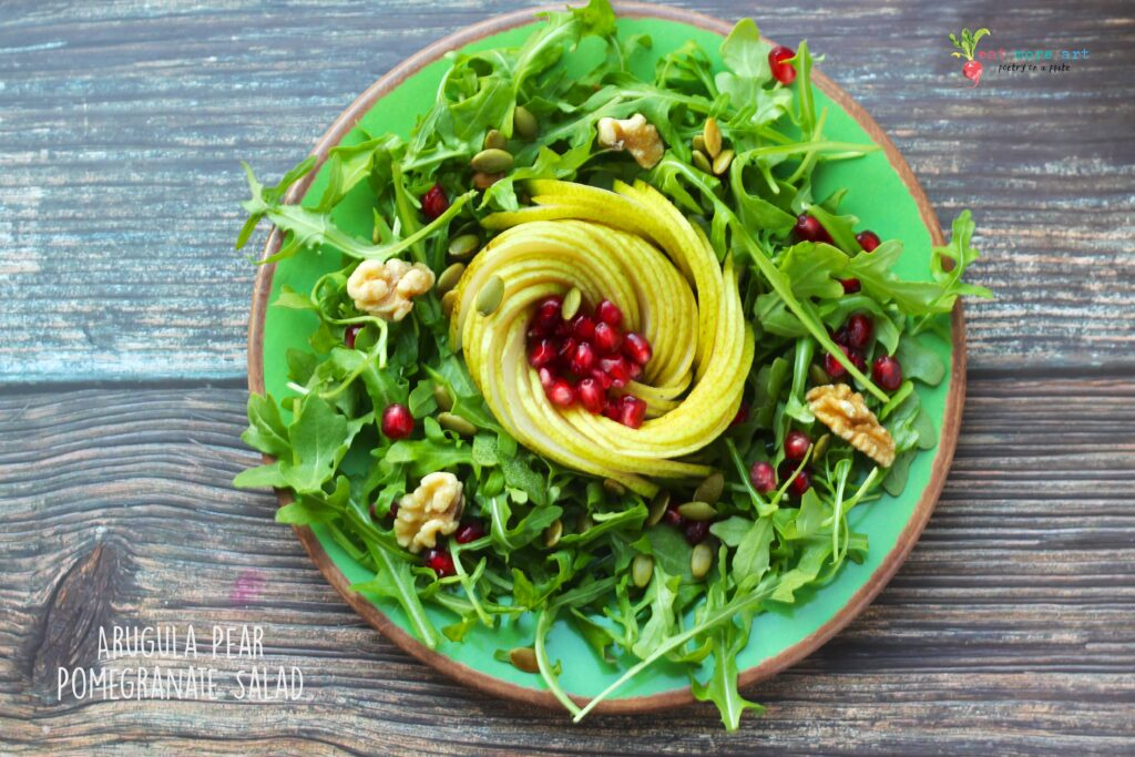 An overhead shot of arugula pear pomegranate salad