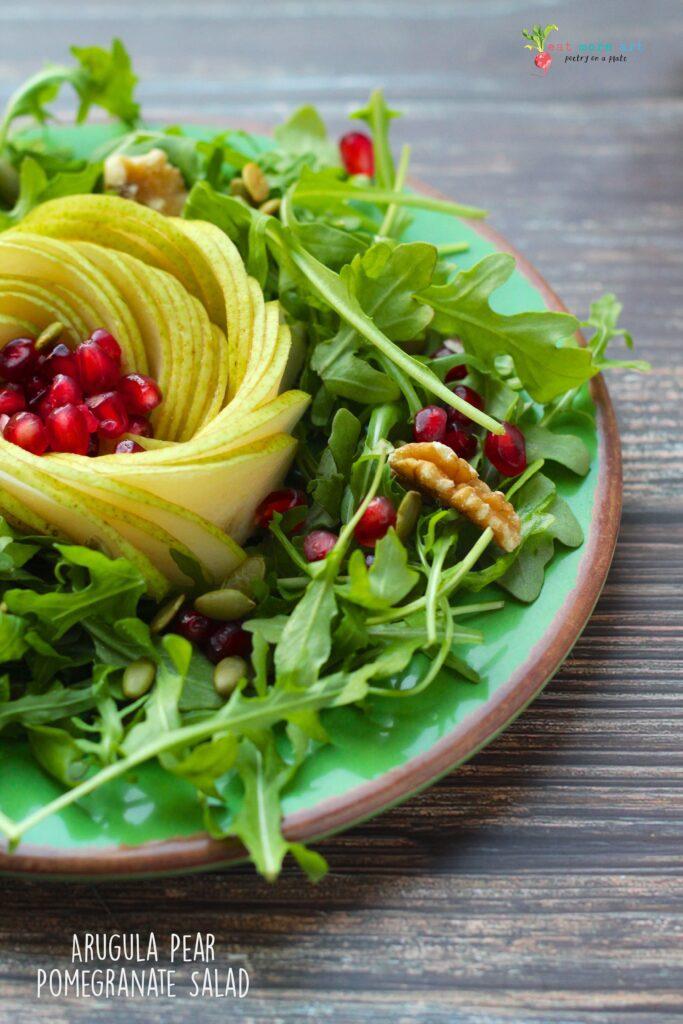 A close up side shot of arugula pear pomegranate salad