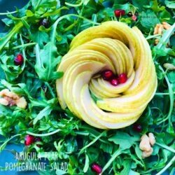 A closeup shot of arugula pear pomegranate salad