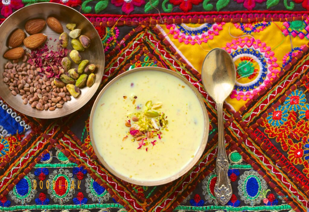An overhead shot of a bowl of doodhpak over a colorful backdrop