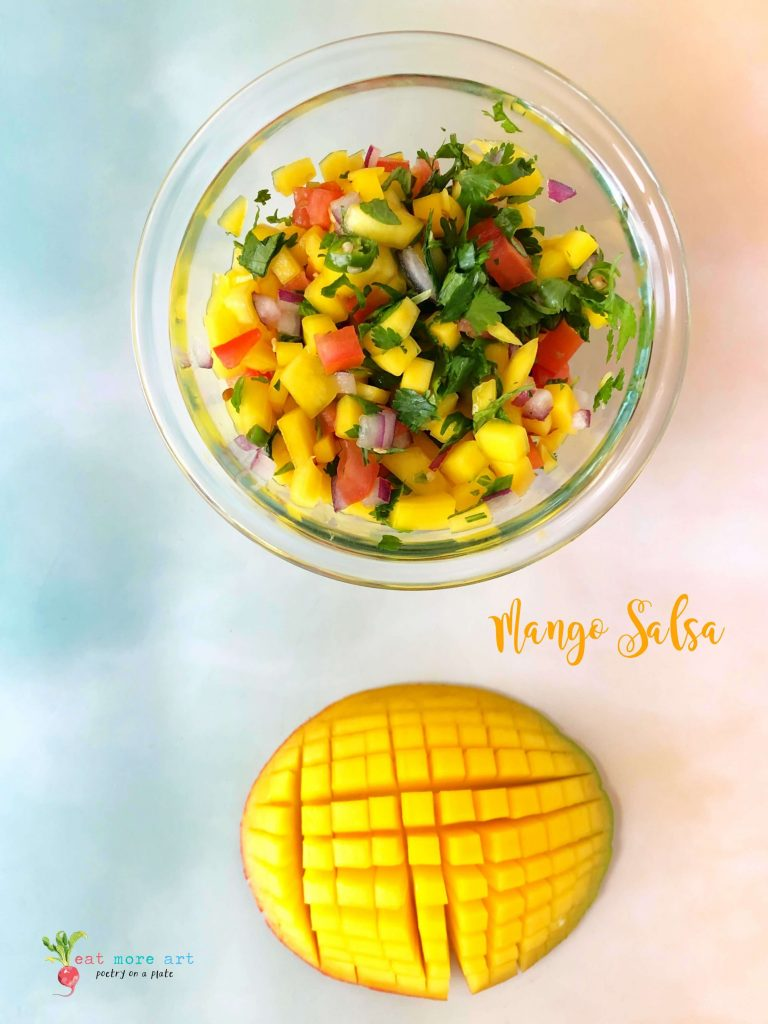 An overhead shot of a bowl of mango Salsa along with cut mango