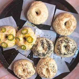 an overhead shot of pre-baked bagels with various toppings